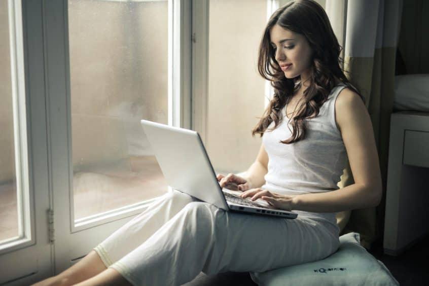 Woman sitting in window on laptop